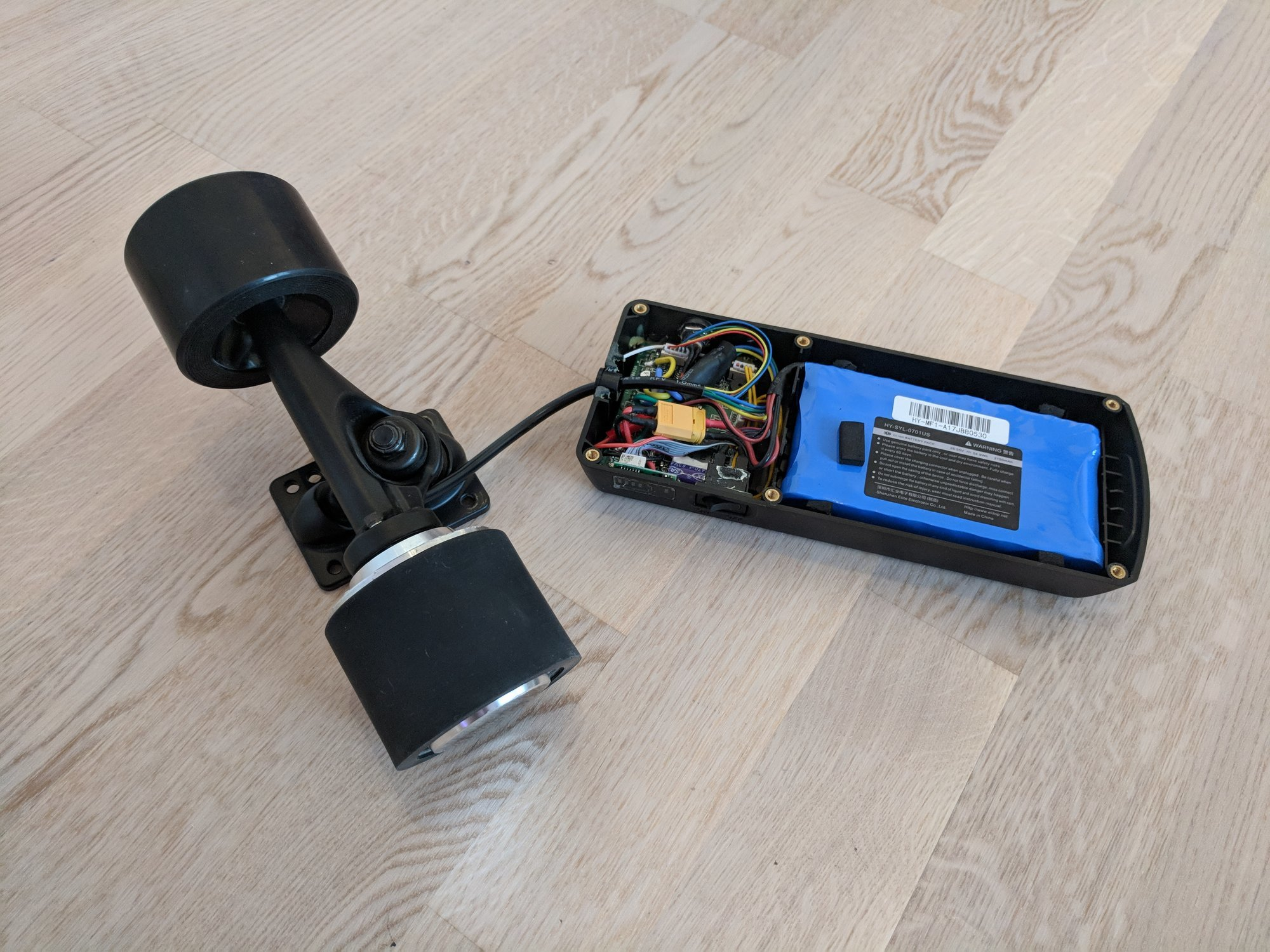The drive train of the electric skateboard connected to the complete electronics with battery pack in the enclosing